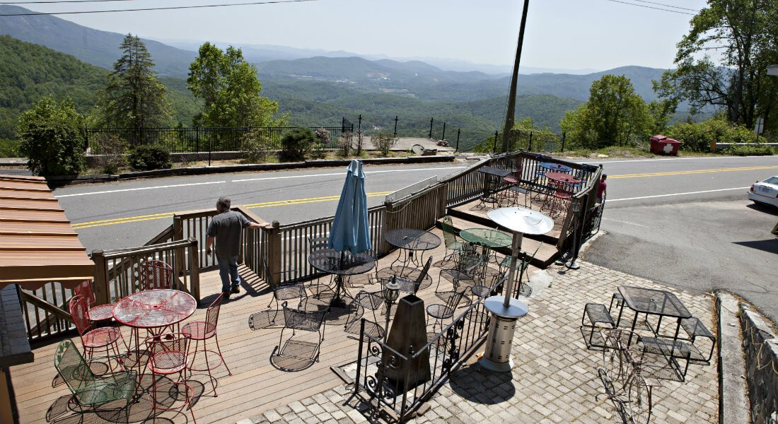 Deck with wood and paver floor, several metal tables and chairs and mountain views
