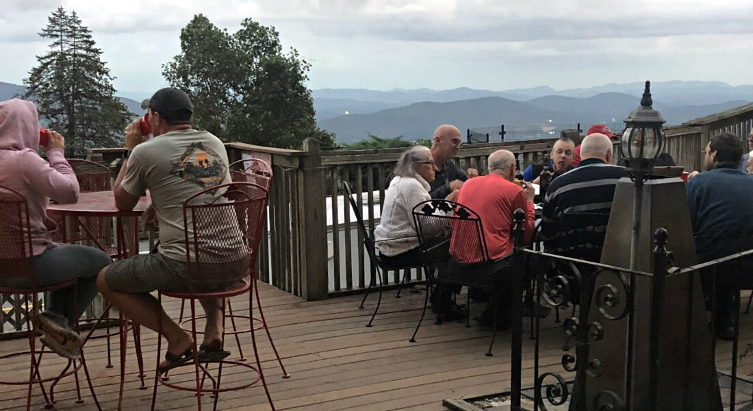 Several people sitting around patio tables on the deck amidst mountain views