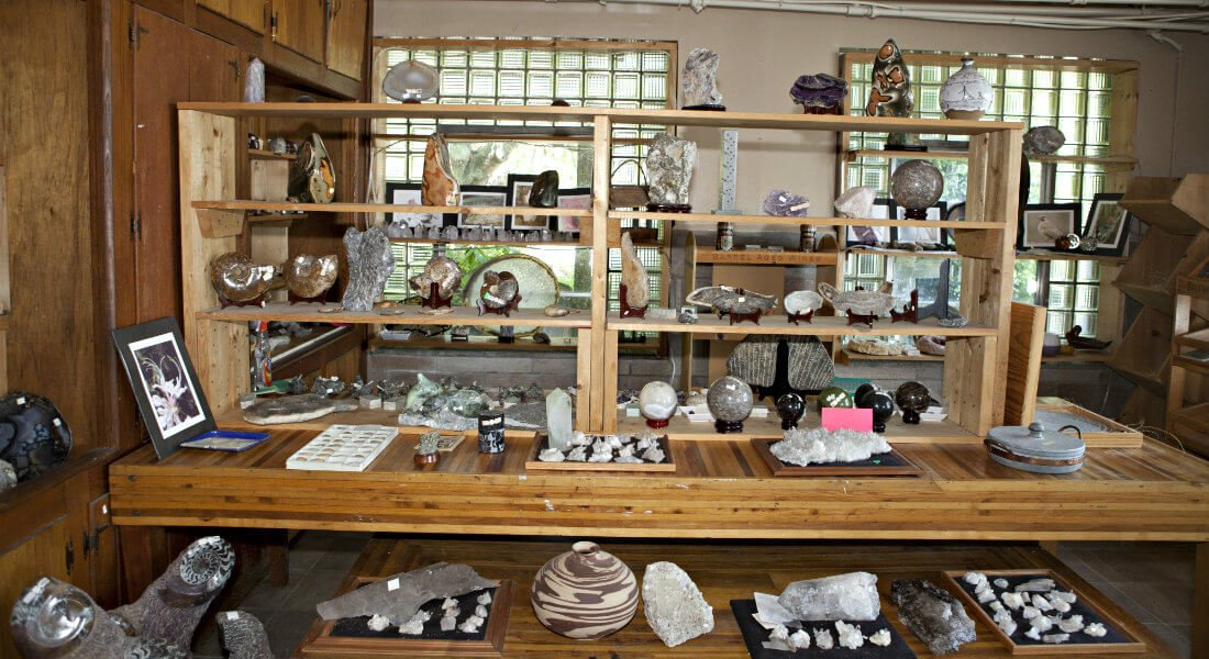 Inside the thrift store with wood shelves topped with decorative items made with stones