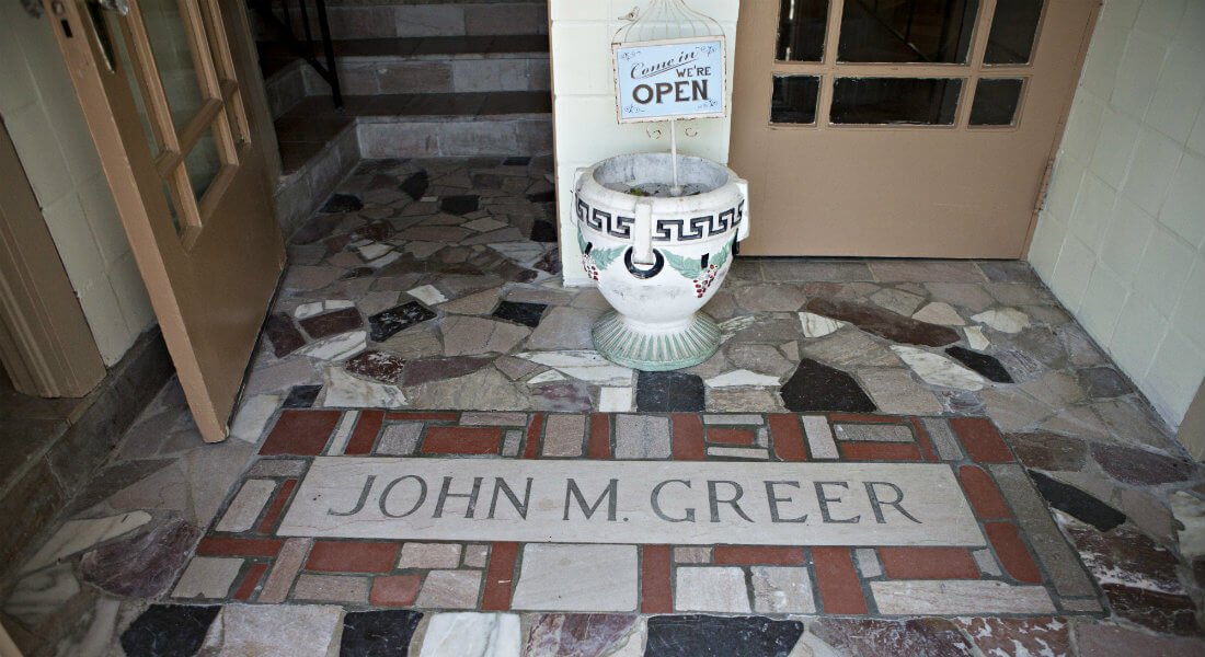 Double glass entry with John M. Greer etched in the stone floor