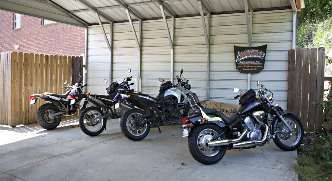 Four motorcycles parked under a metal carport