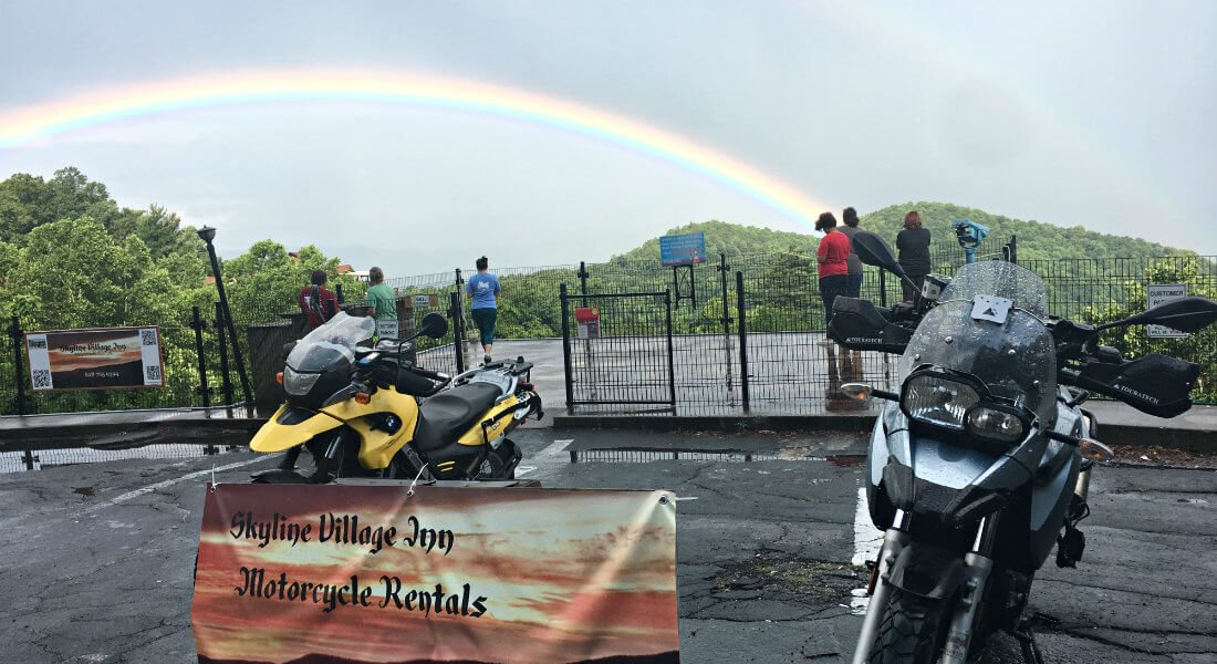 Several people outside the inn admiring a beautiful rainbow over the mountains and a motorcylces for rent sign in the forefront