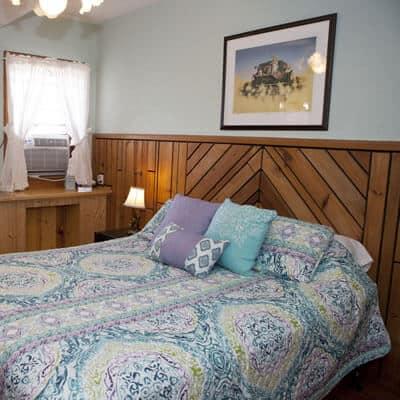 Guest room with light blue walls, small window with air conditioning unit and one bed with nightstand