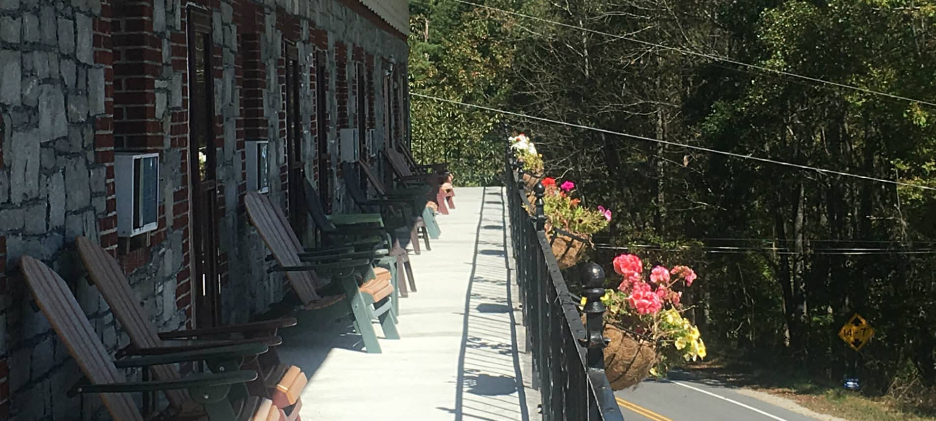 Upper balcony of the inn lined with adirondak chairs and flower baskets surrounded by trees