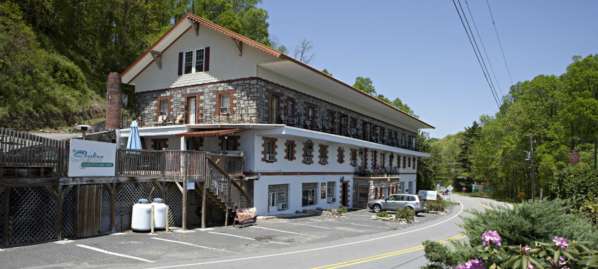 Exterior view of inn with four stories, front entry parking, side deck and surrounded by trees