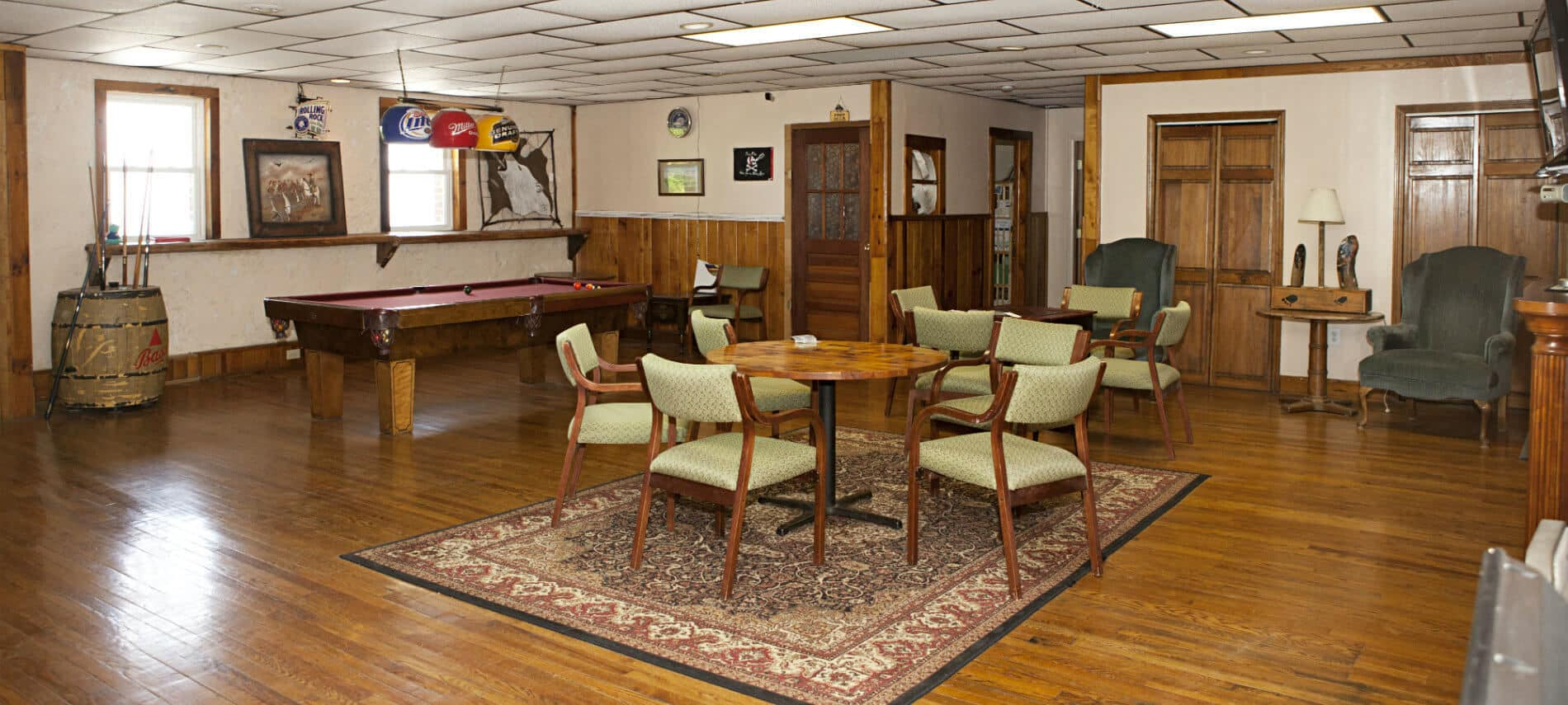 Spacious recreation room with hardwood floor, sitting chairs, table and chairs, pool table and TV