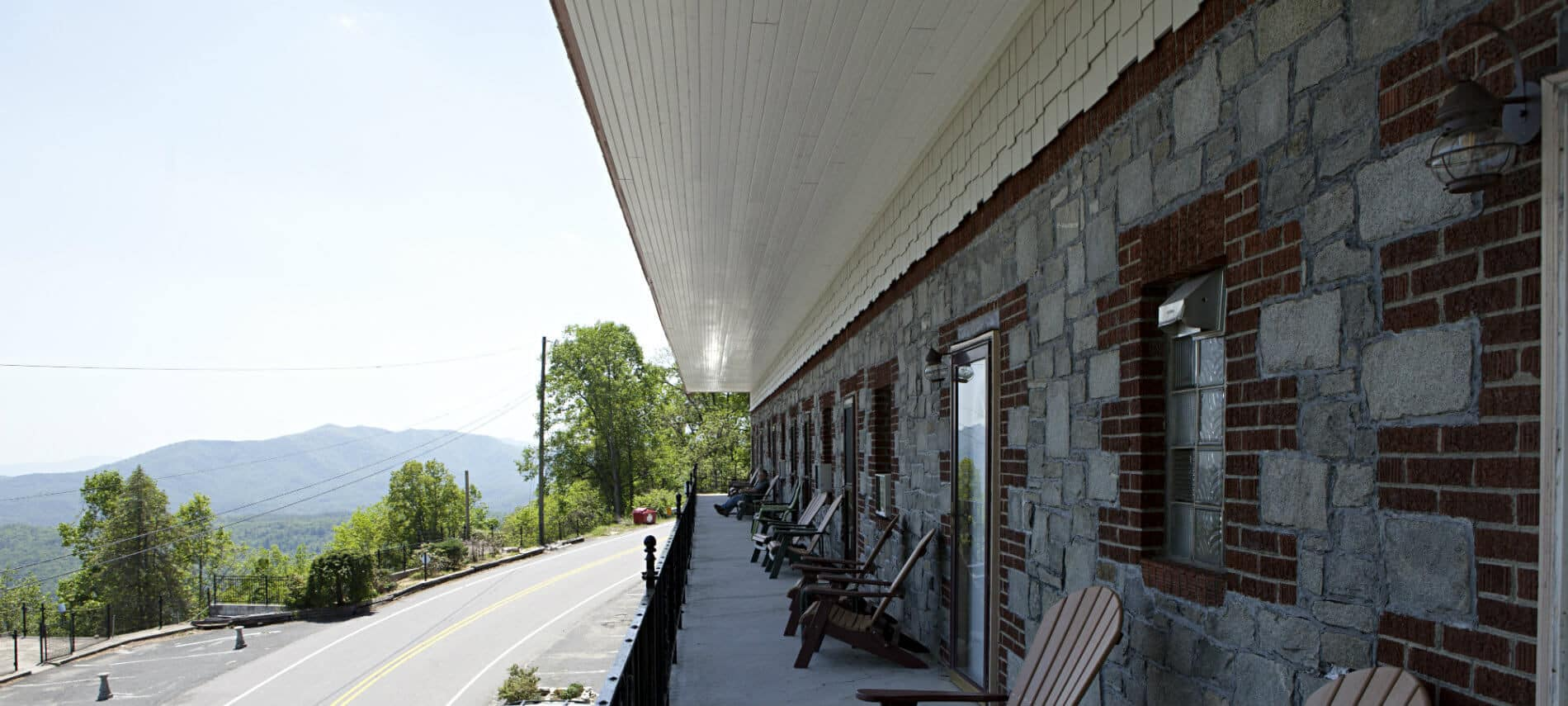 Balcony of the inn with stone and brick wall and a long row of adirondack chairs next to each guest room door