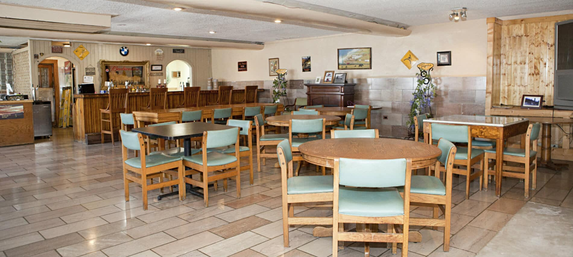 Spacious tavern with tile floor, several tables and chairs, and a bar with stools