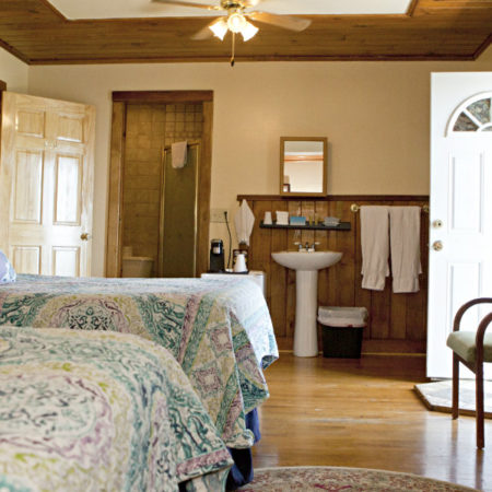 Guest room with ceiling fan, wood floor, two beds, in-room sink, guest abth, and dresser