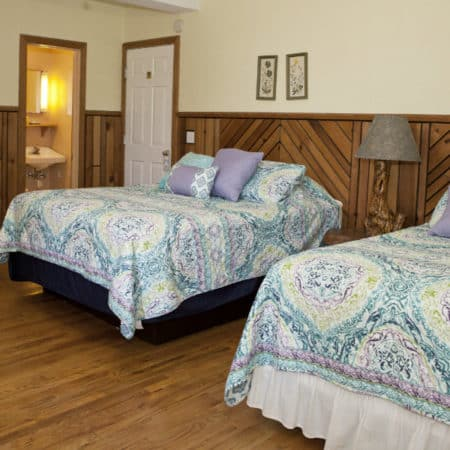Spacious guest room with wood floor, two beds with nightstand, small drop-leaf table with two chairs, and guest bath