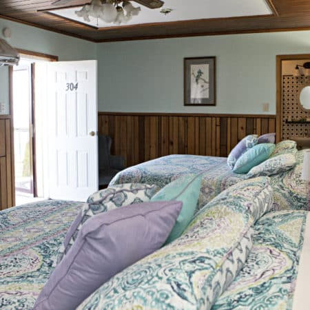 Guest room with ceiling fan, two beds, flat screen tv, and guest bath