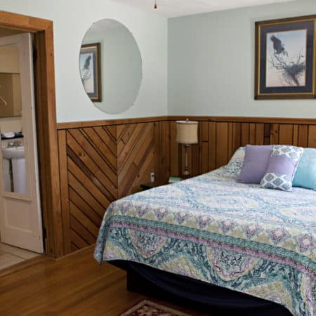 Guest room with wood floor, partial paneling, one bed, exterior door, wingback chair and oval mirrors