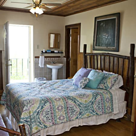 Guest room with wood floor, exterior door, in-room pedestal sink, one bed, and flat screen tv