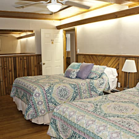 Guest room with wood floor, partial paneling, two beds with nightstand, lamp and ceiling fan