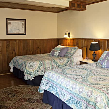 Guest room with wood floor, partial paneling, two beds with nightstand, reading lamps and TV