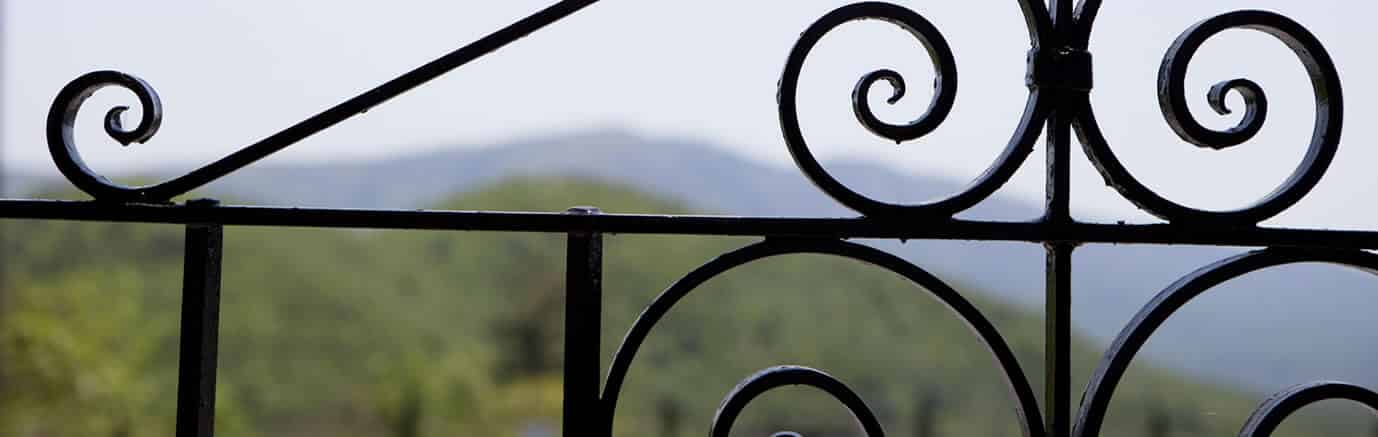 Blurry view of distant mountains through a black metal scrolled railing