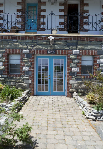 Front exterior of the inn with partial brick and stone, a paver entry sidewalk, and turquoise glass double doors