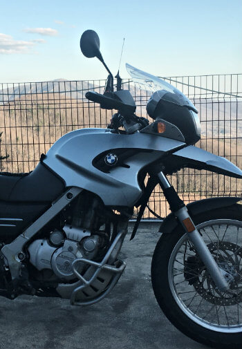 Black and silver motorcycle standing in front of a fence with mountain range in background