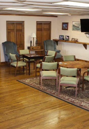 Recreation lounge with two upholstered wing chairs and tables and chairs for cards and games