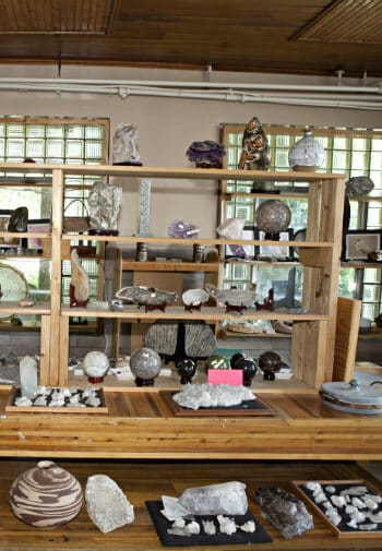 Wood shelves with various items for sale, like large decorative rocks in different shapes and sizes