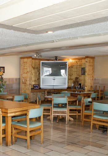 Corner of tavern with large TV and several wood tables with wood and turquoise chairs